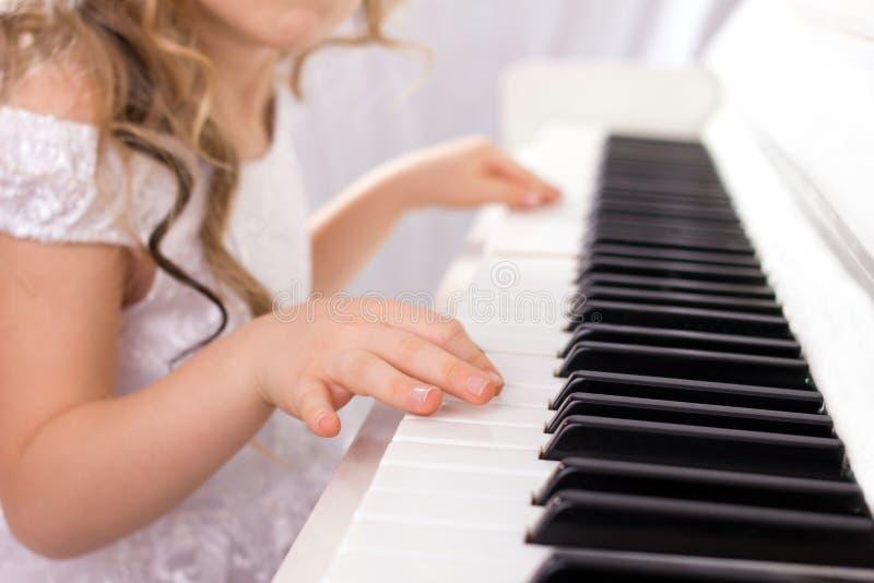 Liten flicka och piano royaltyfri fotografi