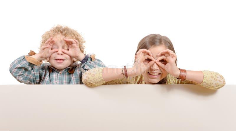Liten flicka och pojke som ser till och med imaginärt fotografering för bildbyråer