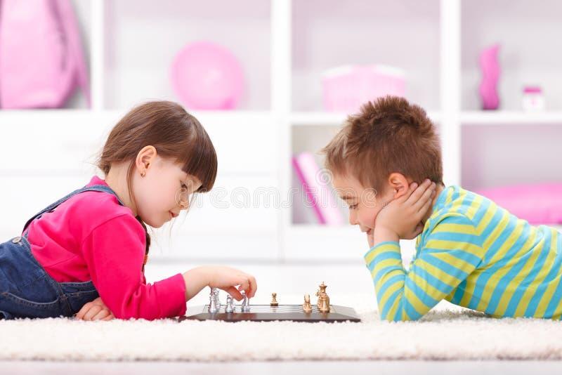 Liten flicka och pojke som spelar schack royaltyfri foto