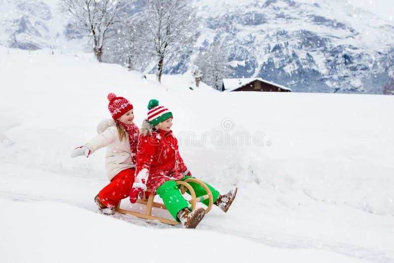 Liten flicka och pojke som tycker om släderitt Sledding för barn Litet barnunge som rider en pulka Barnlek utomhus i snö Lurar sl arkivbild