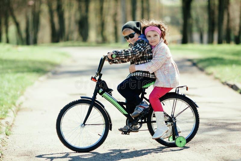 Liten flicka- och pojkeridning på cykeln tillsammans royaltyfria bilder