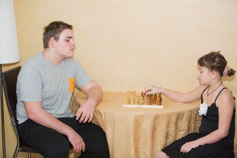Liten flicka och tonårs- pojke som spelar schack arkivfoto