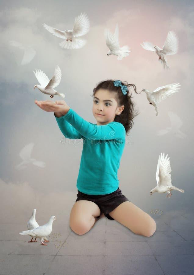 Liten flicka- och vitduvor royaltyfria foton
