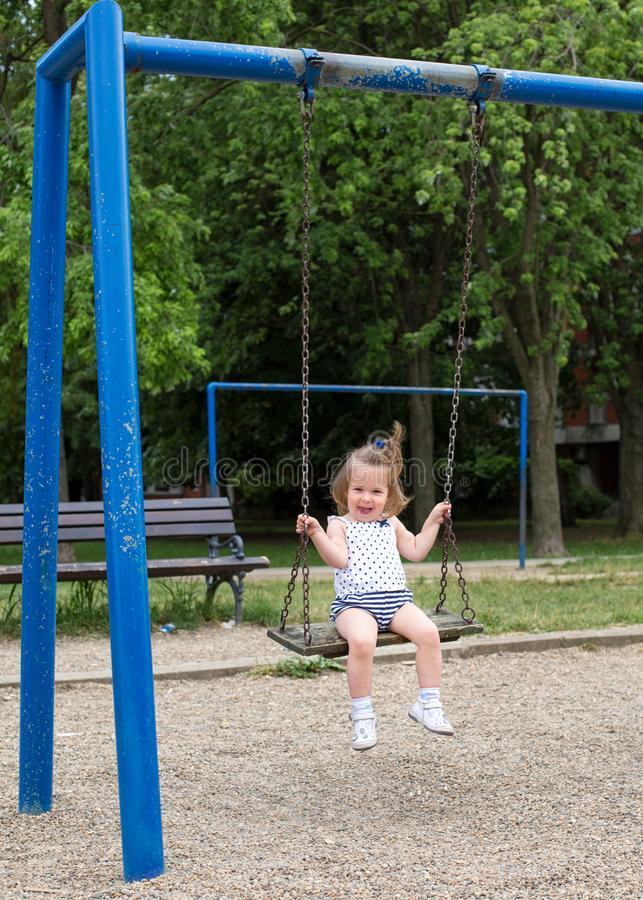 Liten flicka på att svänga för lekplats royaltyfria foton