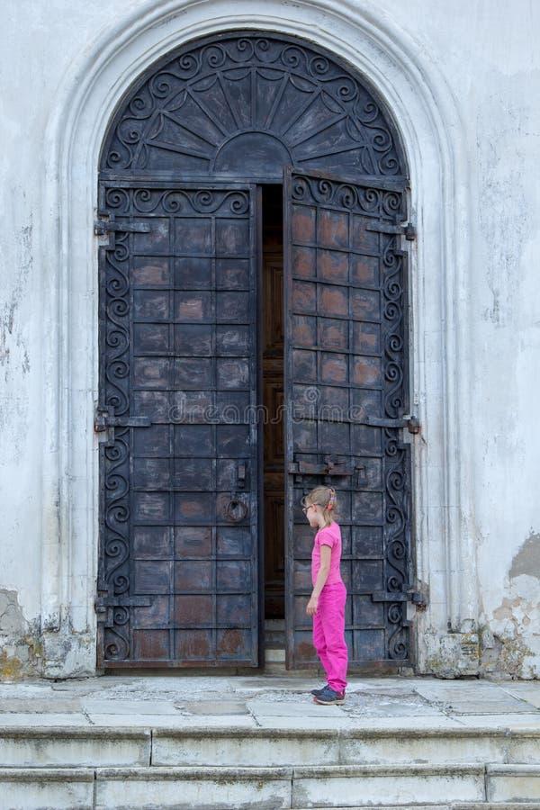 Liten flicka på de enorma metalldörrarna till templet royaltyfria foton