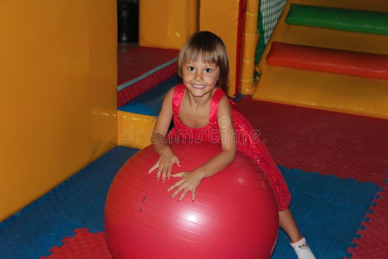 Liten flicka på den stora bollen arkivbild