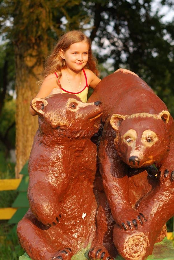 Liten flicka på en brun björn royaltyfri bild