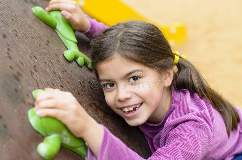 Liten flicka på en klättringvägg arkivbilder
