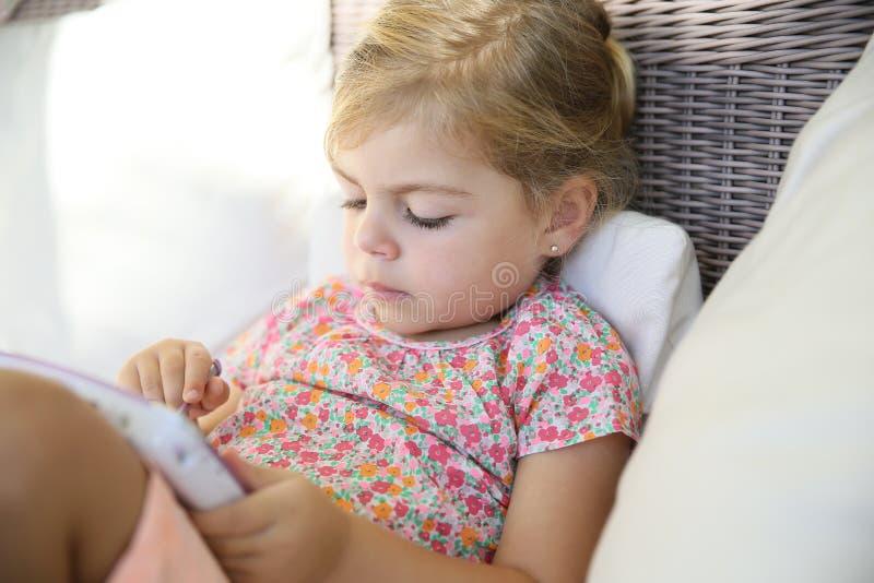 Liten flicka på en minnestavla arkivbild