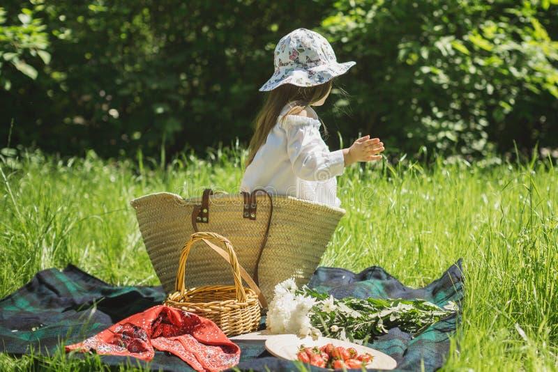 Liten flicka på en sommarpicknick i natur med bär royaltyfri fotografi