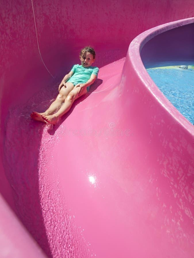 Liten flicka på en vattenglidbana arkivfoto