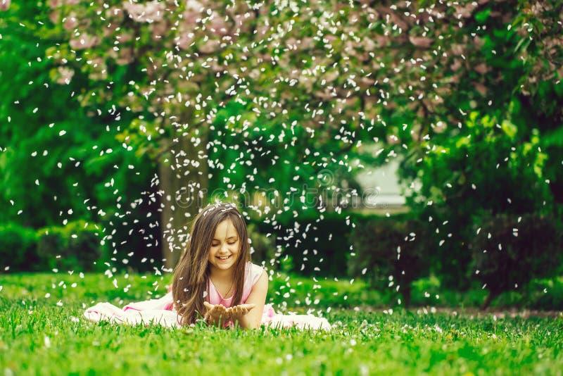Liten flicka på grönt gräs med kronblad arkivfoton