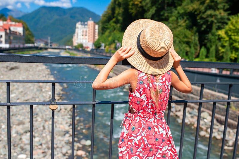 Liten flicka på hatten på invallningen av en bergflod i en europeisk stad arkivbilder