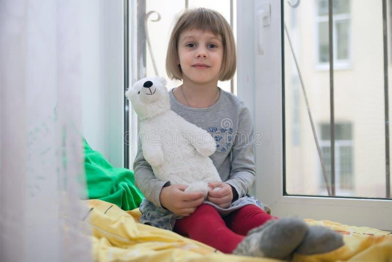 Liten flicka på hemtrevlig fönster-fönsterbräda med björnleksaken arkivbild
