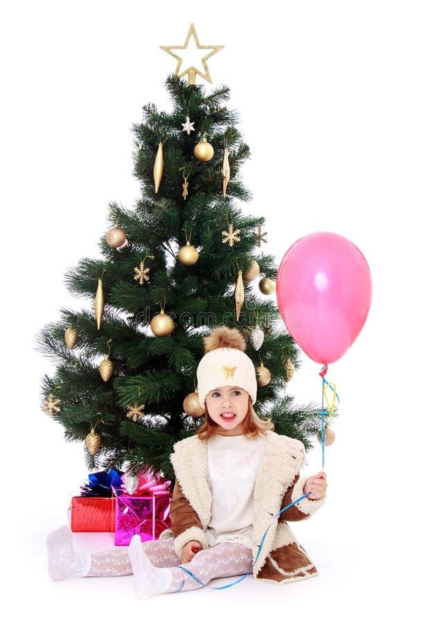 Liten flicka på julgranen arkivbild