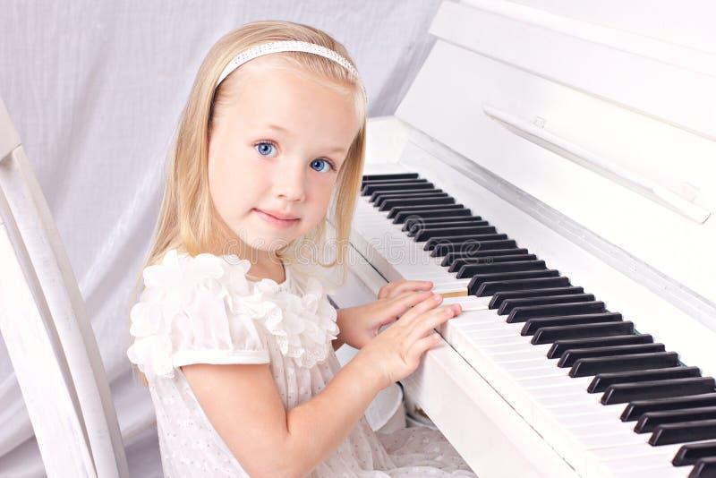 Liten flicka på pianot royaltyfria foton