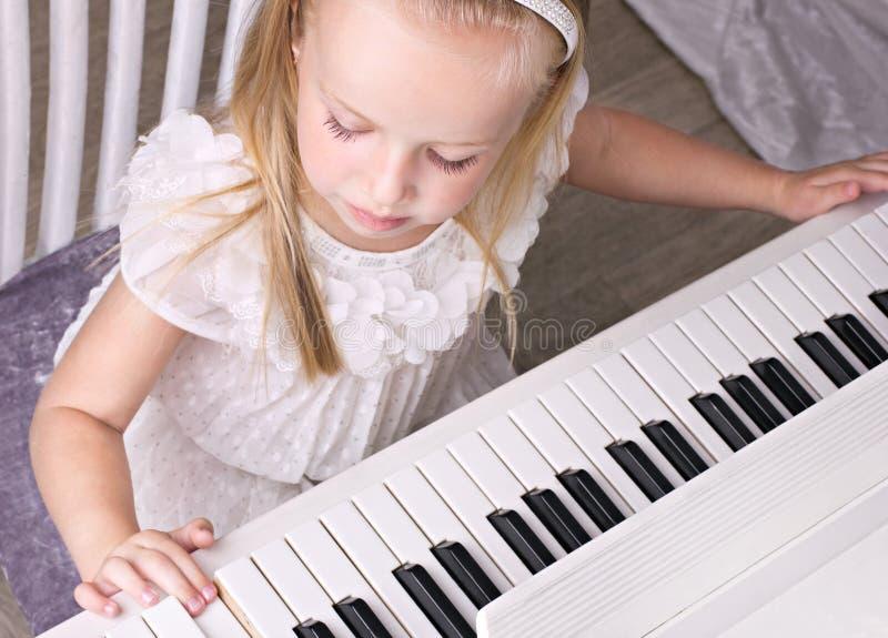 Liten flicka på pianot royaltyfria bilder