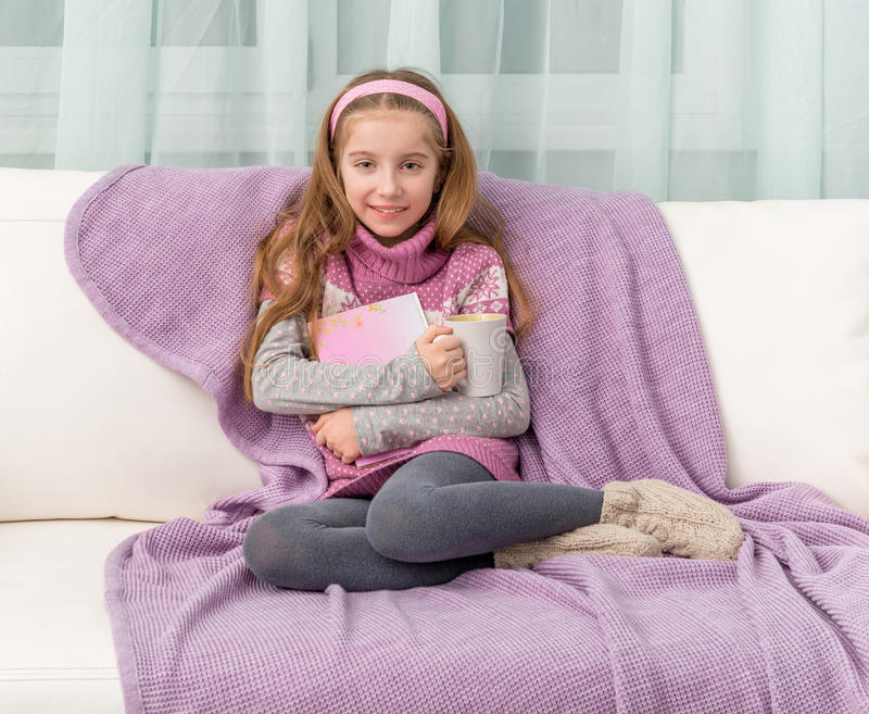 Liten flicka på soffan med boken royaltyfria bilder