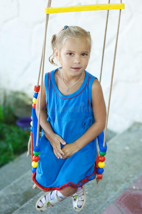 Liten flicka på swing i barn fotografering för bildbyråer