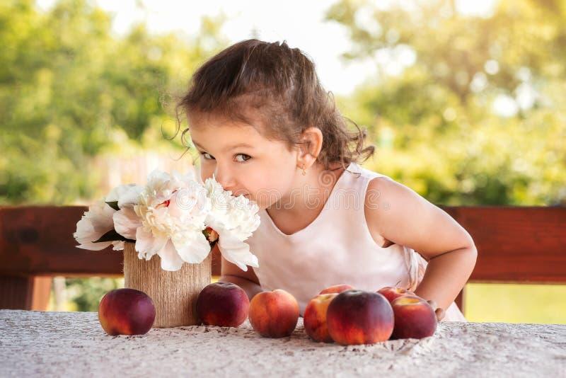Liten flicka på tabellen med persikor på naturen i sommar arkivfoto
