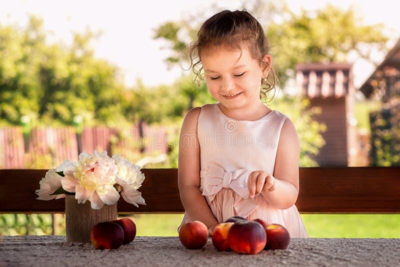 Liten flicka på tabellen med persikor på naturen i sommar arkivfoton