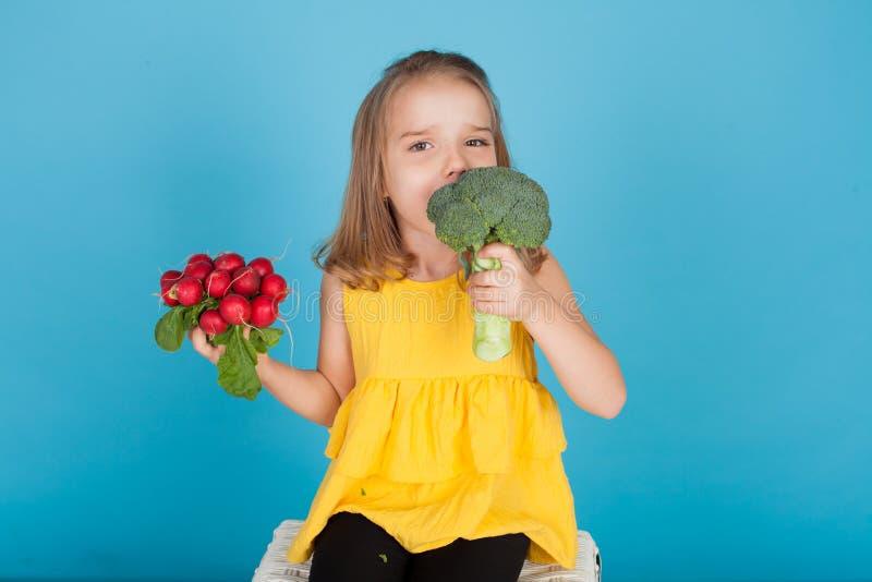 Liten flicka rymma röda rädisor och sunda matgrönsaker för broccoli royaltyfri bild