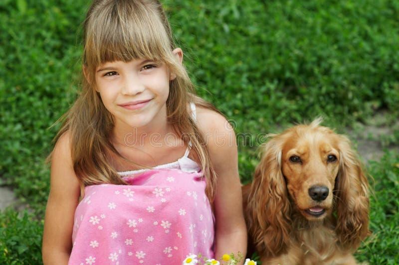Liten flicka sitter i gräset med hunden arkivbild