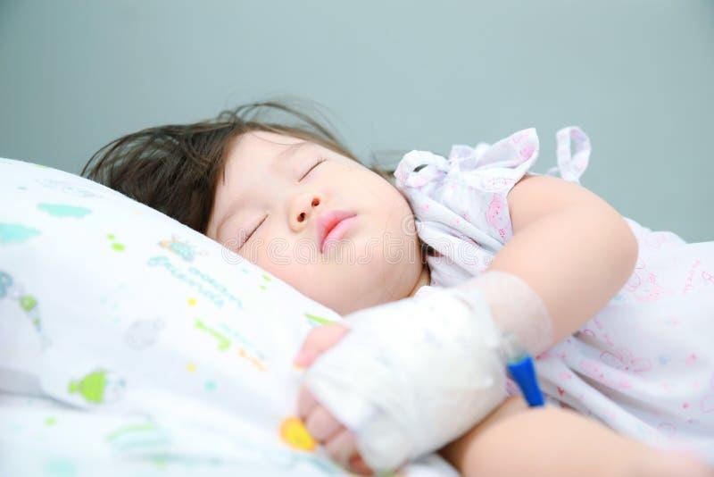 Liten flicka som är sjuk på den sjuka sängen arkivbilder