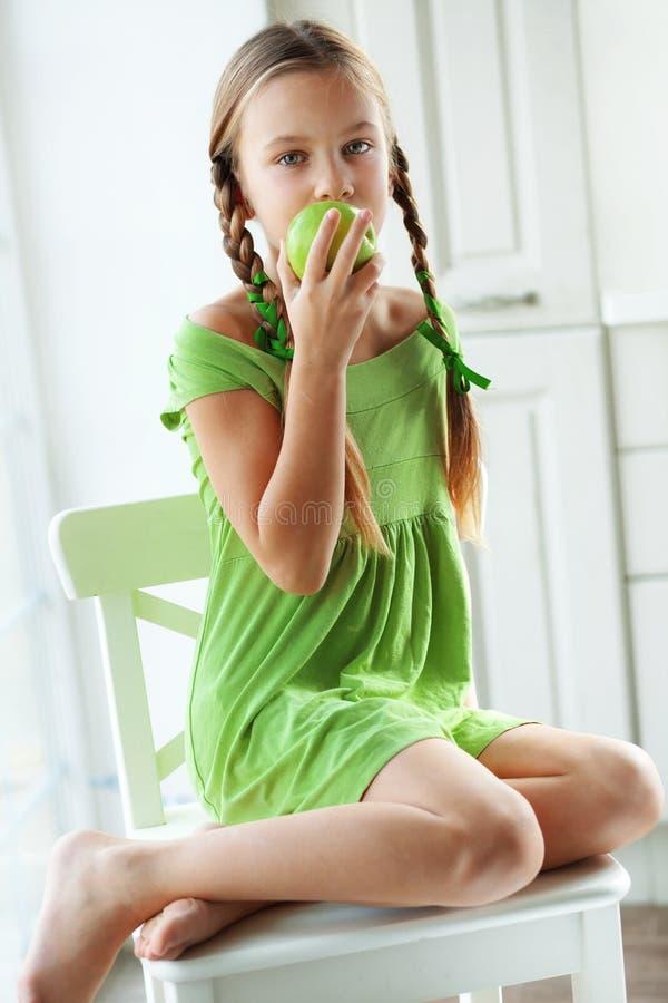 Liten flicka som äter äpplen arkivbild