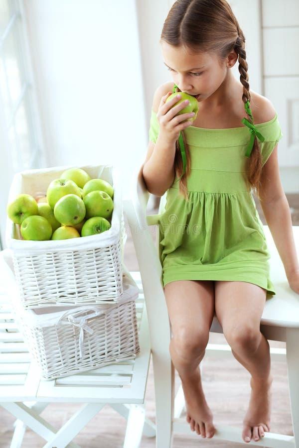 Liten flicka som äter äpplen royaltyfria bilder