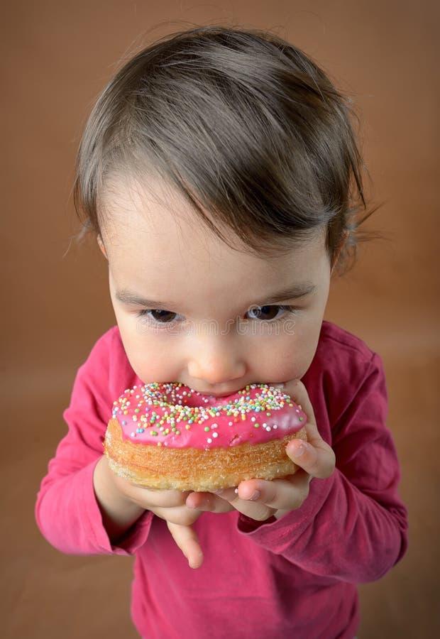 Liten flicka som äter donuts royaltyfri foto