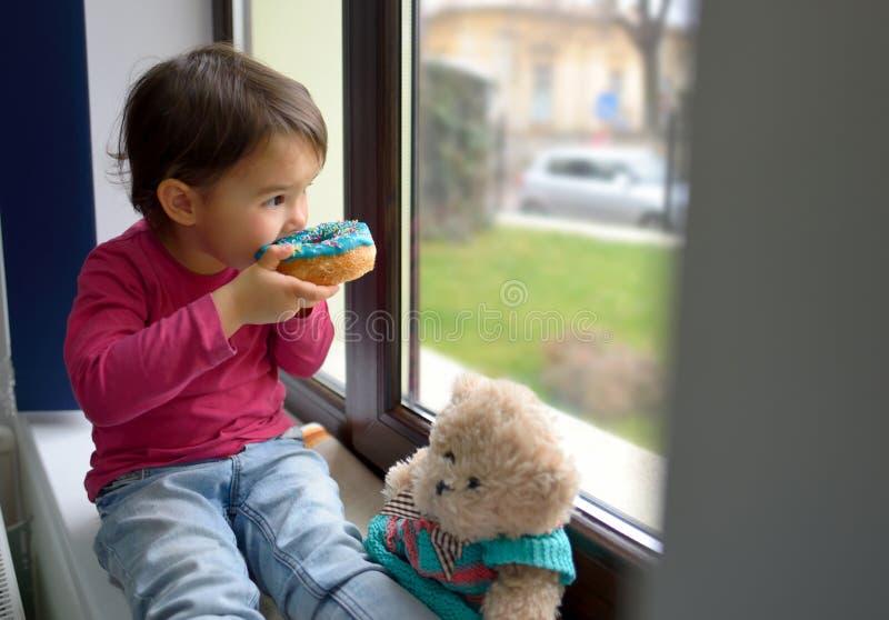 Liten flicka som äter donuts arkivfoto