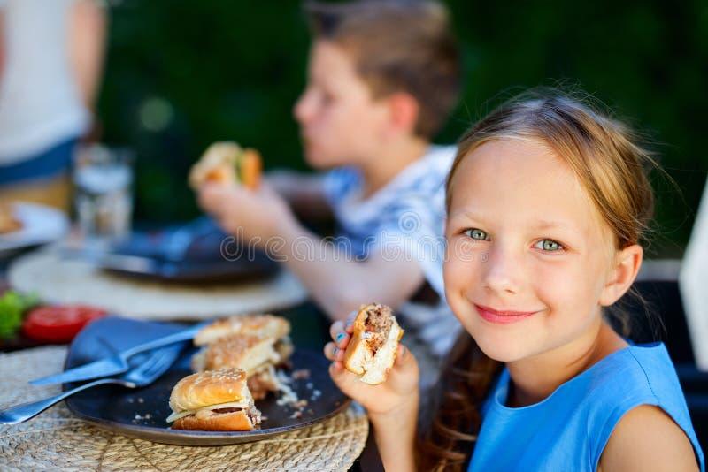 Liten flicka som äter hamburgaren royaltyfri bild