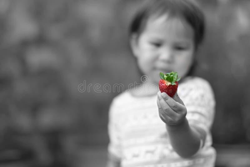 Liten flicka som äter jordgubbar utanför i trädgården royaltyfri bild