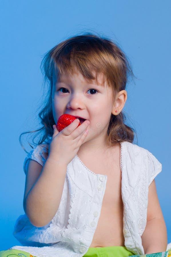 Liten flicka som äter jordgubben arkivfoto