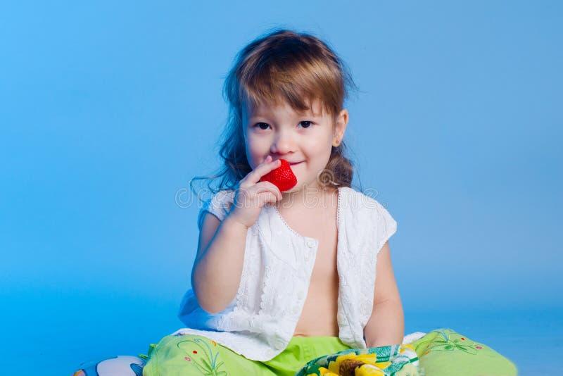 Liten flicka som äter jordgubben royaltyfri foto