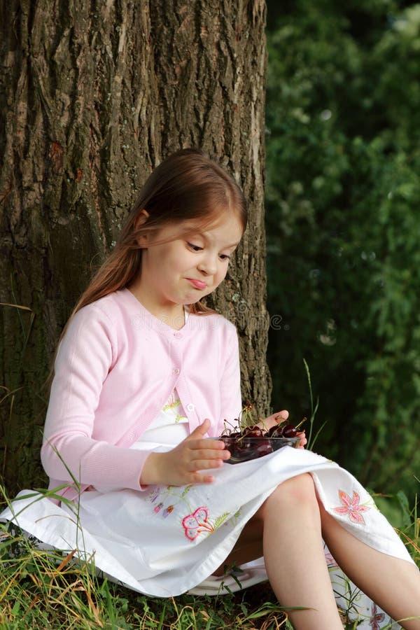 Liten flicka som äter körsbär arkivbild