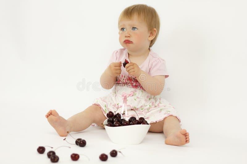 Liten flicka som äter körsbär royaltyfri fotografi