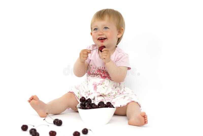 Liten flicka som äter körsbär arkivfoton