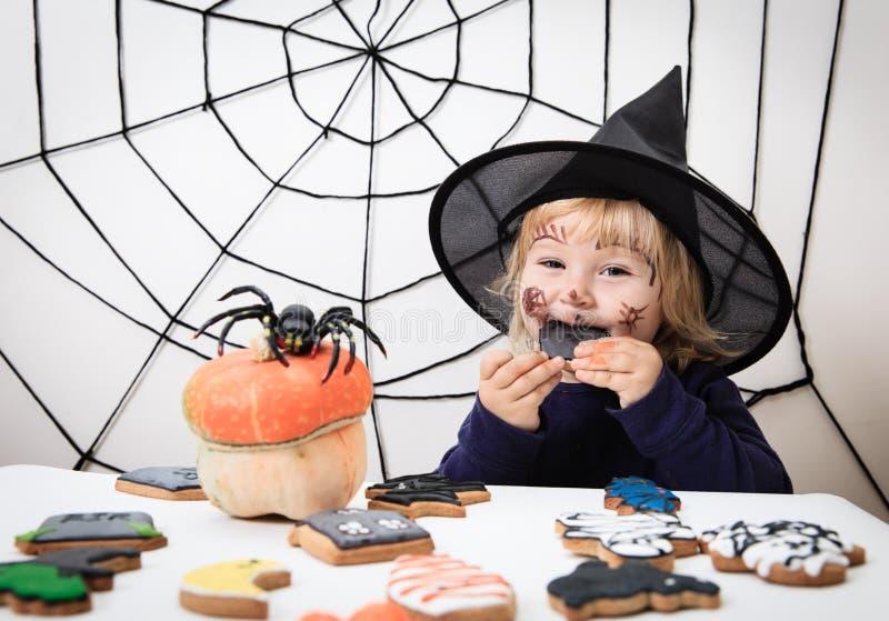 Liten flicka som äter kakor på halloween, ungetrick eller behandling royaltyfri foto