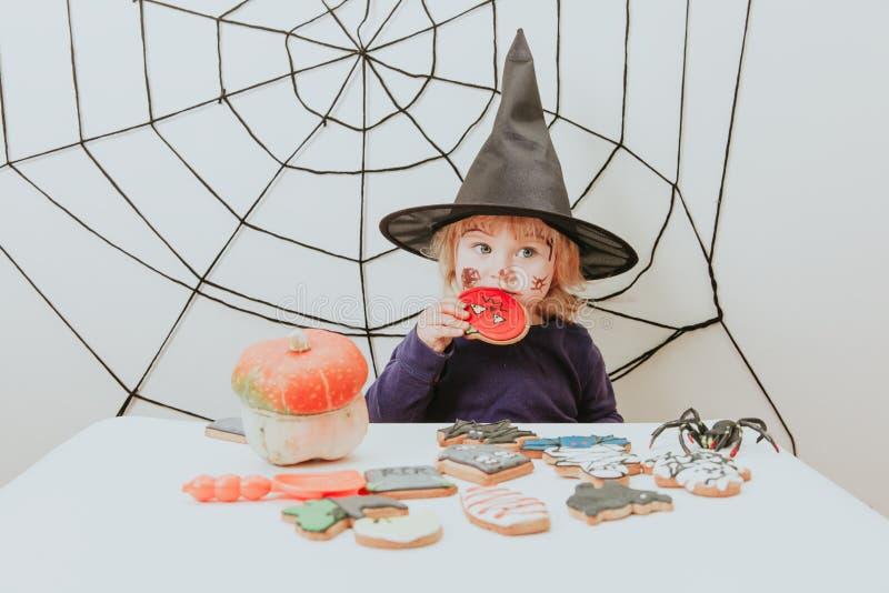 Liten flicka som äter kakor på halloween, ungetrick eller behandling arkivbild