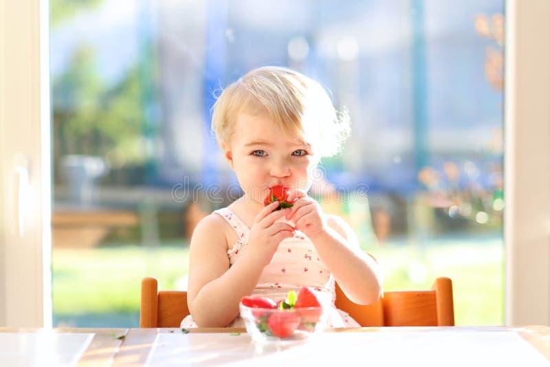 Liten flicka som äter läckra jordgubbar royaltyfria bilder