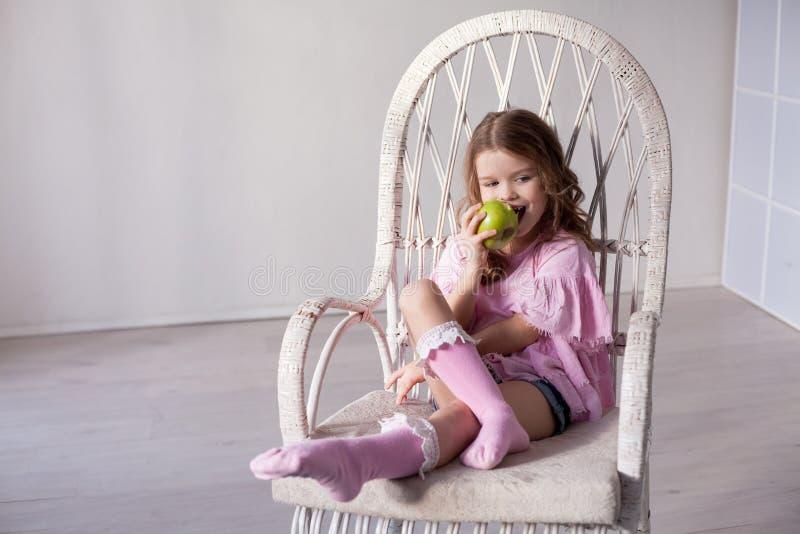 Liten flicka som äter mogen grön Apple sund mat royaltyfria foton