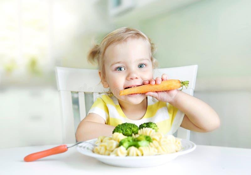 Liten flicka som ?ter moroten, gr?nsaker, sund mat N?ring f?r barn` s royaltyfri bild