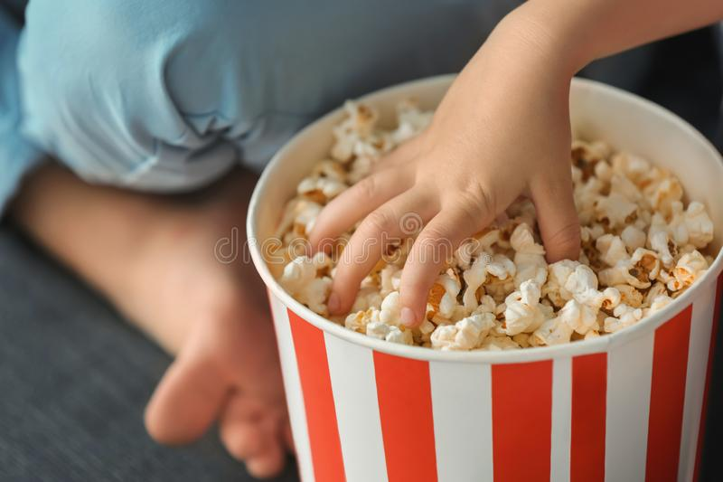 Liten flicka som äter popcorn, medan hålla ögonen på TV hemma, closeup arkivfoton