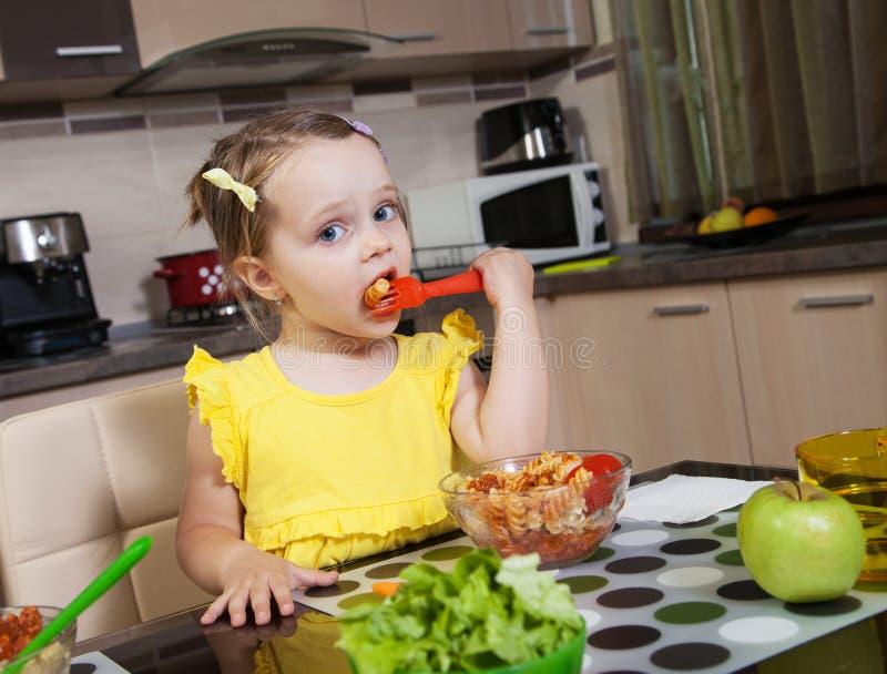 Liten flicka som äter sund mat i köket fotografering för bildbyråer