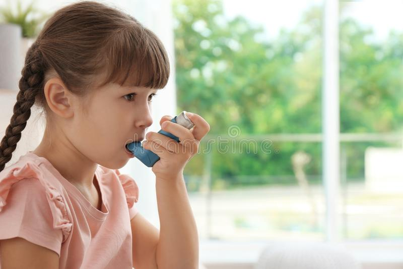Liten flicka som använder astmainhalatorn royaltyfria foton