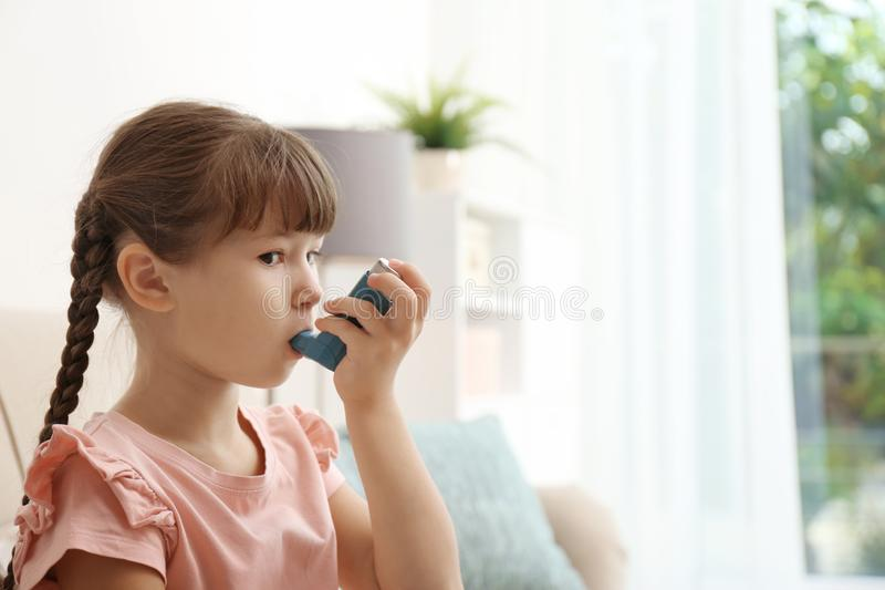 Liten flicka som använder astmainhalatorn fotografering för bildbyråer
