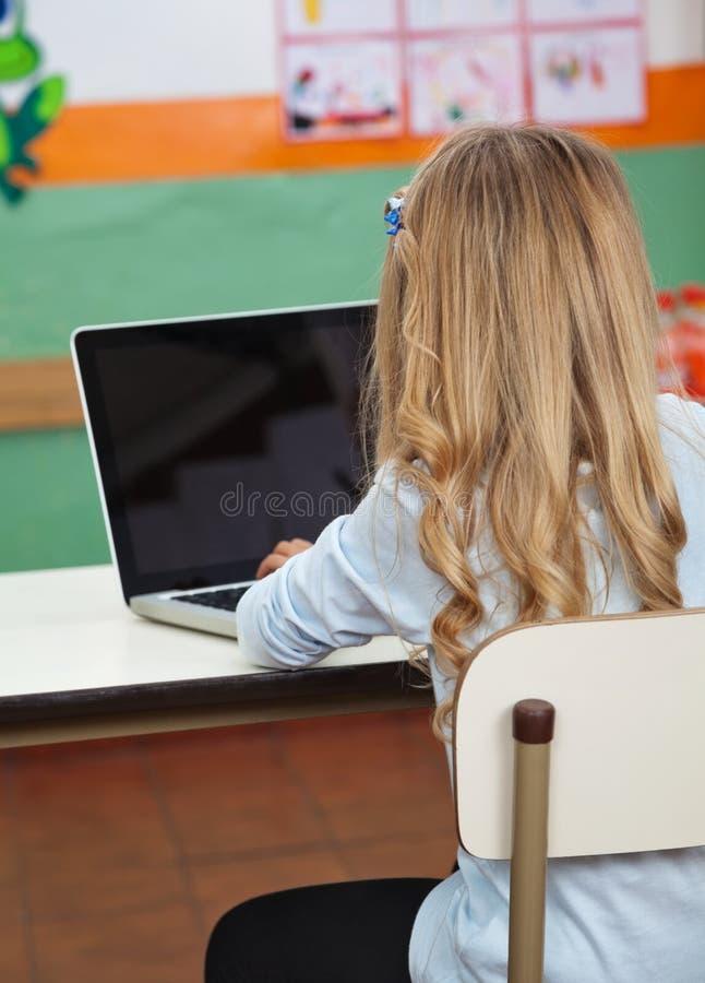 Liten flicka som använder bärbara datorn i förträning arkivbilder