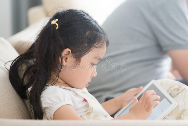 Liten flicka som använder den digitala minnestavlan royaltyfri fotografi
